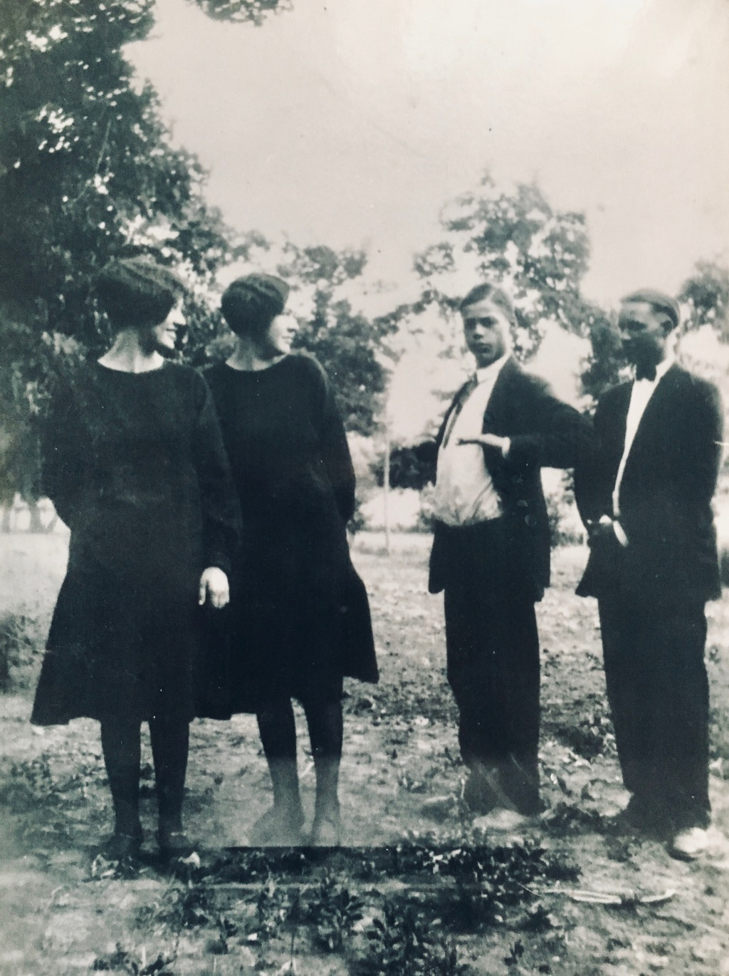 Two young ladies and two young men in funeral attire.